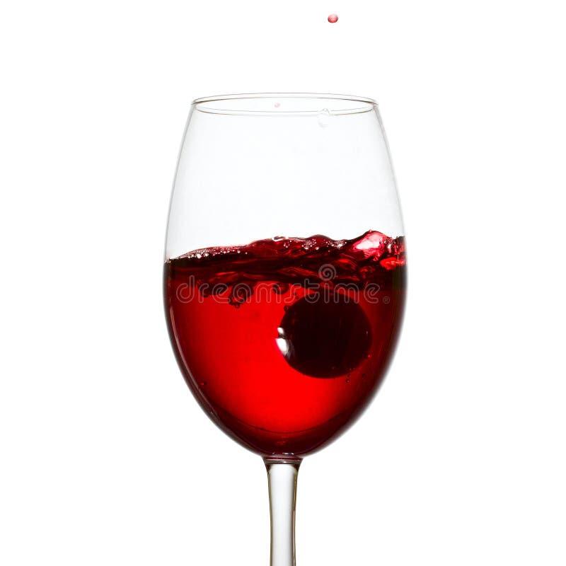 Vetro elegante di vino rosso con la spruzzatura della bevanda alcolica immagine stock libera da diritti
