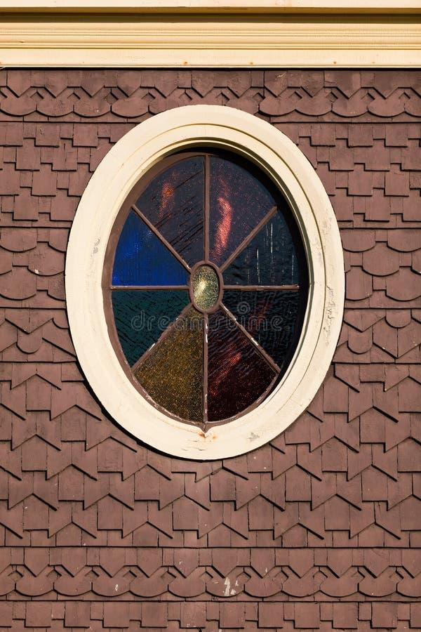 Vetro macchiato ovale su un cottage del pan di zenzero immagini stock libere da diritti