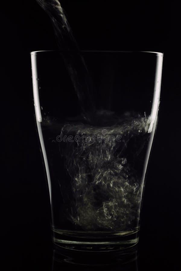 vetro/vetro in quali scorrimenti dell'acqua su un fondo nero L'acqua è pulita - il vetro è trasparente Un vetro su un backgrou ne immagine stock