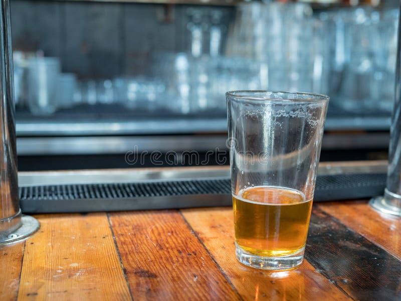 Vetro quasi vuoto della pinta di birra che si siede sul controsoffitto per l'ultima c fotografie stock