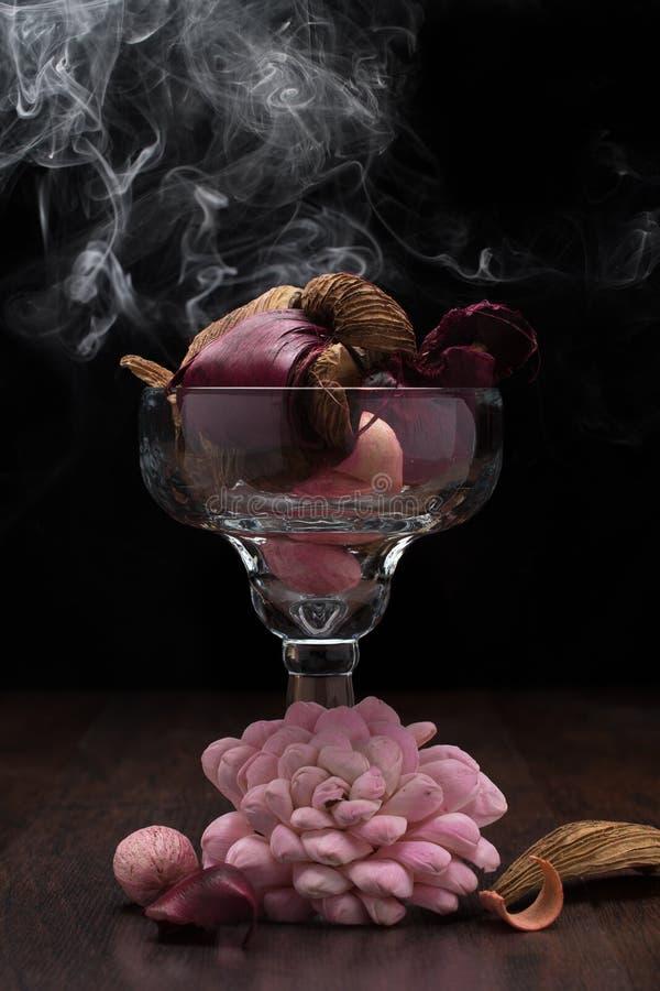 Vetro riempito di marrone, di rosa e di potpourri rossi con fumo sulla tavola di legno con fondo nero L'illuminazione di Rembrand immagine stock libera da diritti