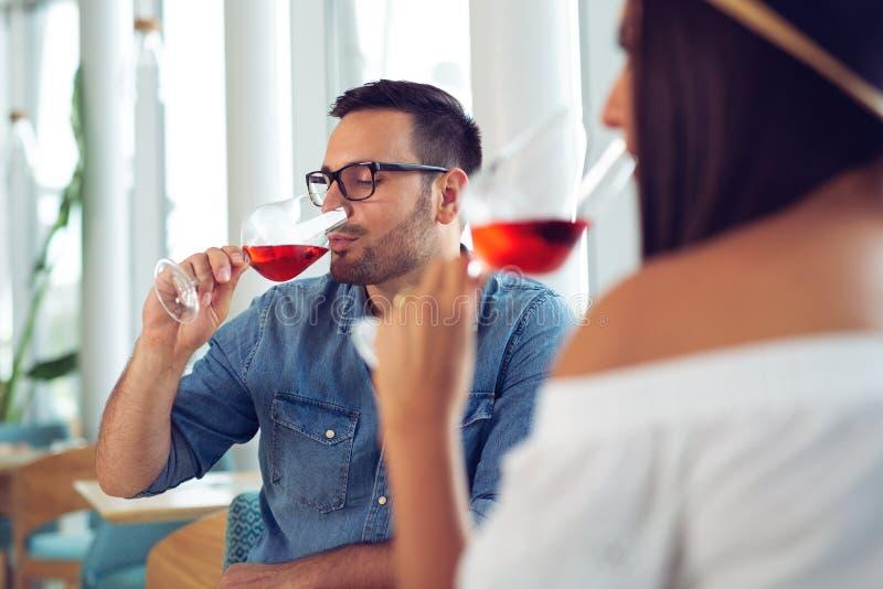 Vetro romantico della bevanda della data delle coppie felici di vino rosso al ristorante fotografia stock libera da diritti