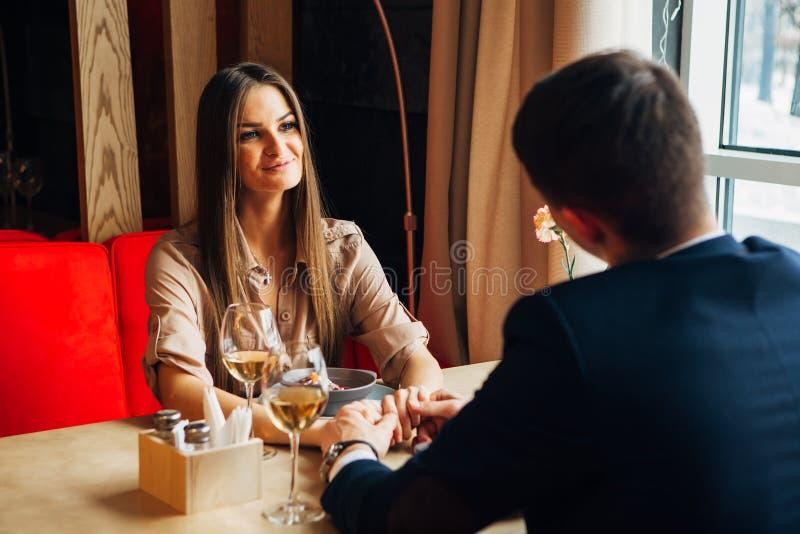 Vetro romantico della bevanda della data delle giovani coppie felici di vino bianco al ristorante, celebrante giorno di S. Valent fotografia stock
