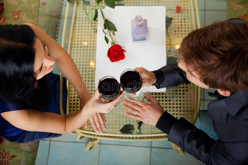Vetro romantico della bevanda della data delle giovani coppie felici di fotografia stock