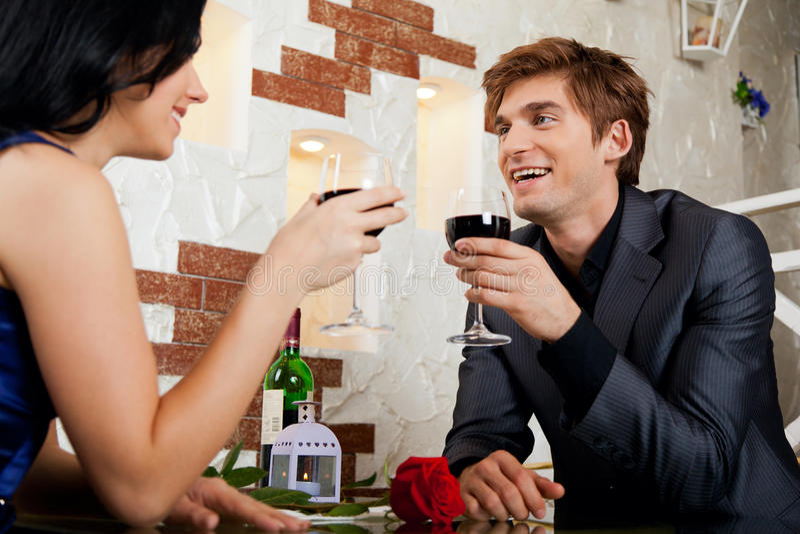 Vetro romantico della bevanda della data delle giovani coppie felici di immagini stock