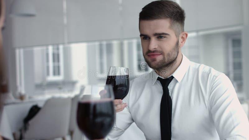 Vetro romantico della bevanda della data delle giovani coppie felici di vino rosso al ristorante, celebrante giorno di S. Valenti immagine stock