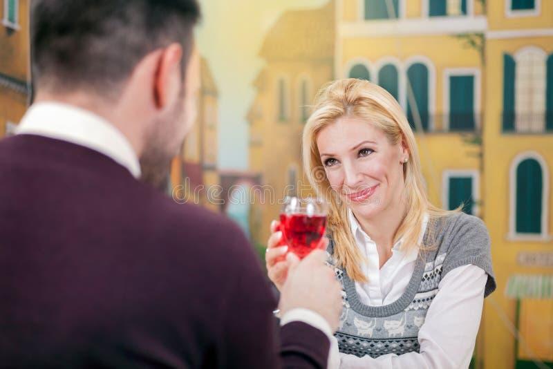 Vetro romantico della bevanda della data delle giovani coppie felici di vino rosso a riposo fotografia stock