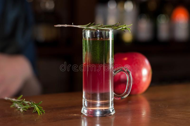 Vetro sparato con la bevanda multicolore dell'alcool e rosmarini sulla mela rossa vicina fotografia stock libera da diritti