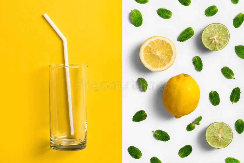 Vetro su fondo colorato spaccato, giallo vuoto e bianco con la disposizione delle foglie di menta, del limone e della limetta fotografie stock libere da diritti