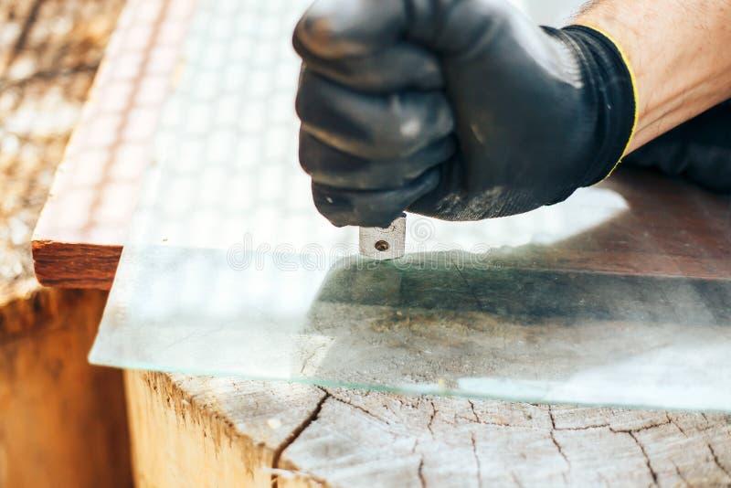 Vetro tagliato dalla taglierina di vetro Mani dell'uomo con i guanti che tengono taglierina di vetro fotografie stock