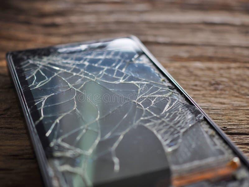 Vetro tagliato smartphone nero sul bordo di legno anziano nel concetto di manutenzione mobile, danno accidentale immagini stock libere da diritti