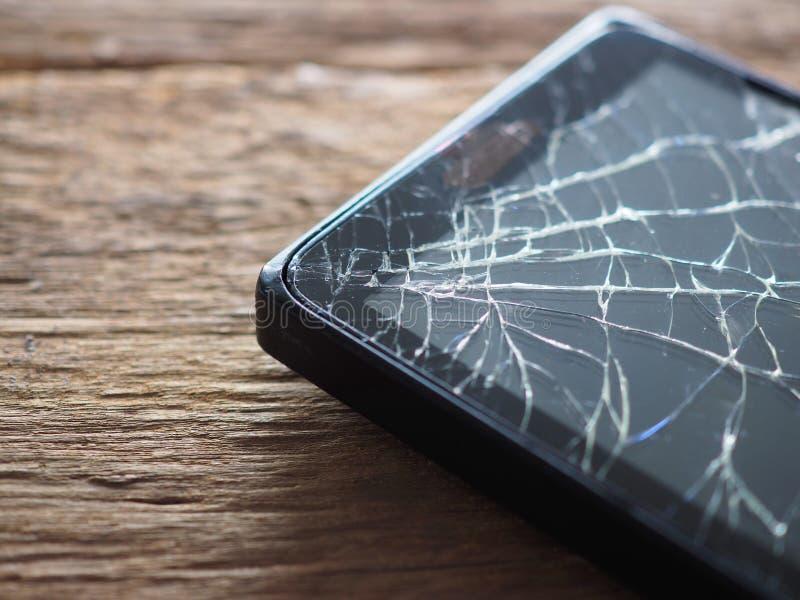 Vetro tagliato smartphone nero sul bordo di legno anziano nel concetto di manutenzione mobile, danno accidentale fotografie stock libere da diritti