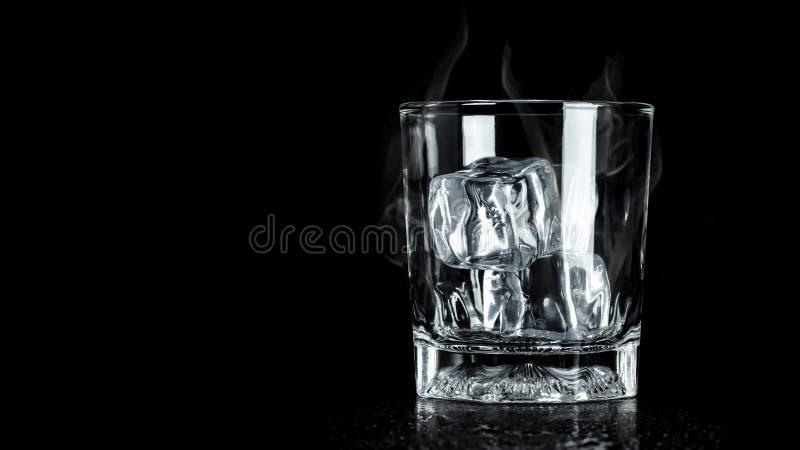 Vetro vuoto con il cubetto di ghiaccio su fondo scuro con fumo e spazio di raffreddamento Blocchi di ghiaccio per la bevanda fotografia stock libera da diritti