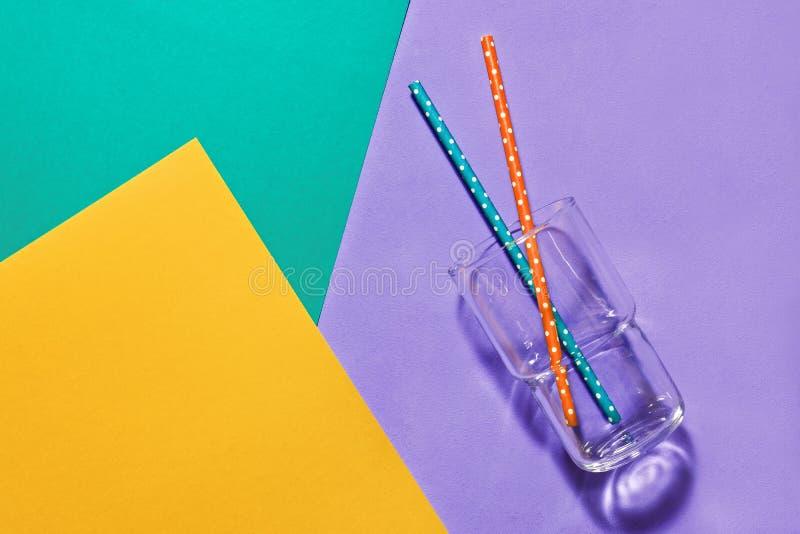 Vetro vuoto con le paglie su un fondo variopinto pastello, concetto minimalista, disposizione piana Concetto di estate e delle be immagini stock libere da diritti