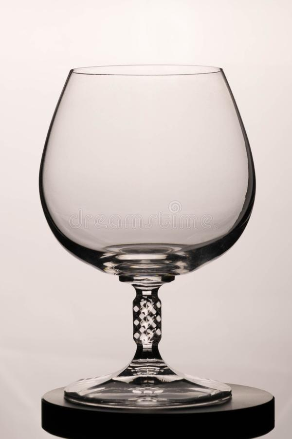 Vetro vuoto del cognac su un fondo bianco fotografia stock libera da diritti