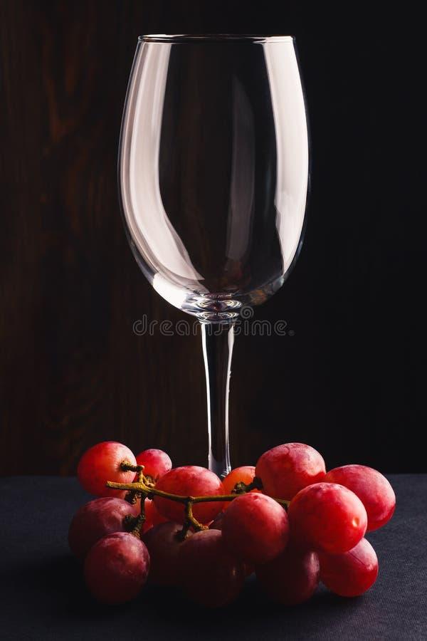 Vetro vuoto per vino ed il mazzo di uva fotografia stock libera da diritti