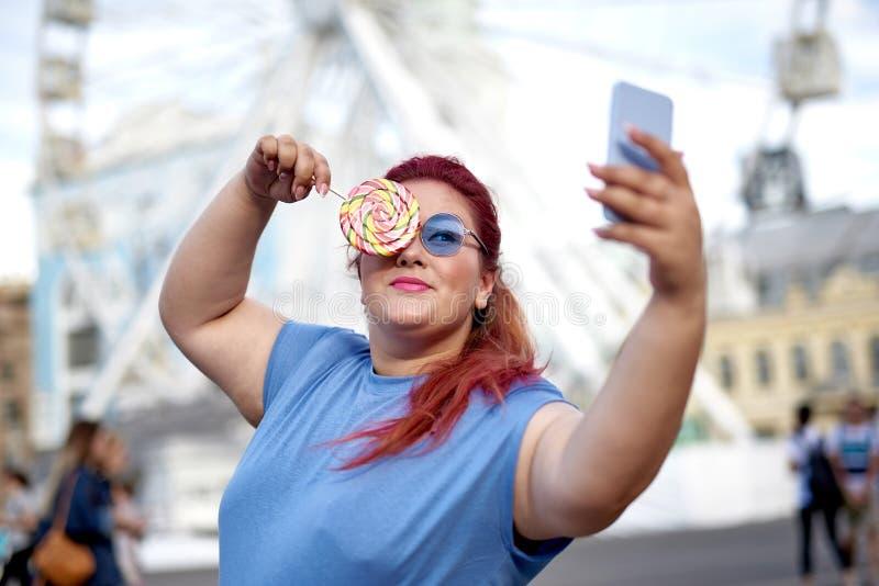 Vette en jonge vrouw die selfie met in hand lolly maken royalty-vrije stock afbeelding