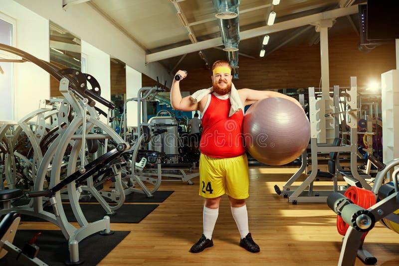 Vette grappige mens in de gymnastiek stock afbeeldingen
