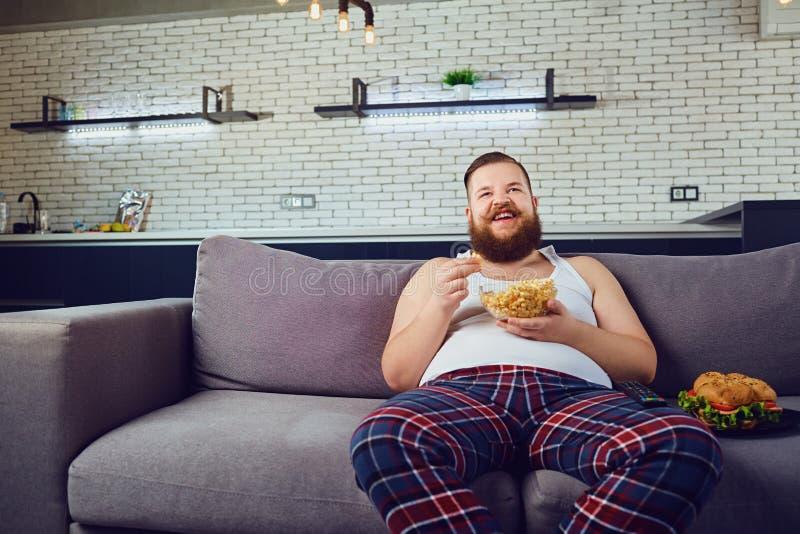 Vette grappige mens die in pyjama's een hamburger thuis eten stock foto