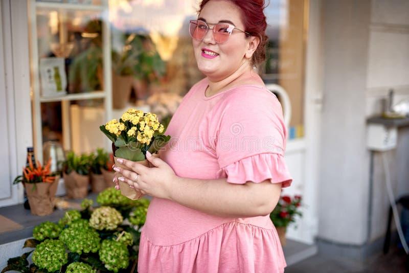 Vette jonge vrouw dichtbij de bloempot van de winkelholding stock foto's