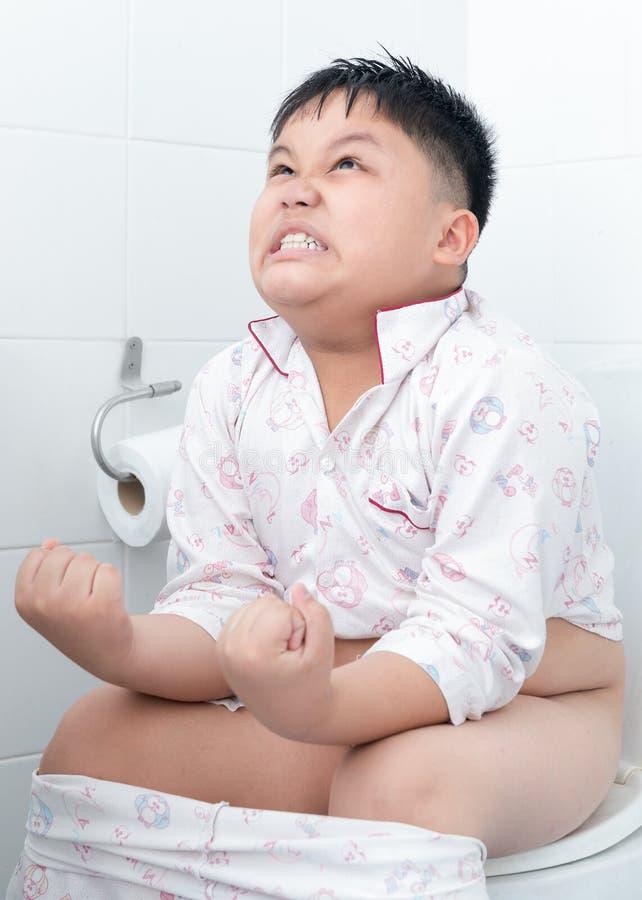 Vette jongenszitting op het toilet stock foto