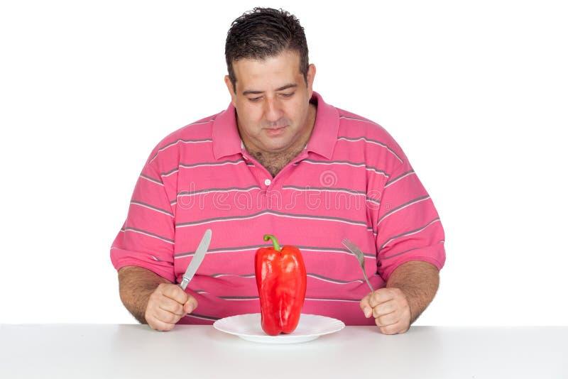 Vette mens die een Spaanse peper eet stock foto