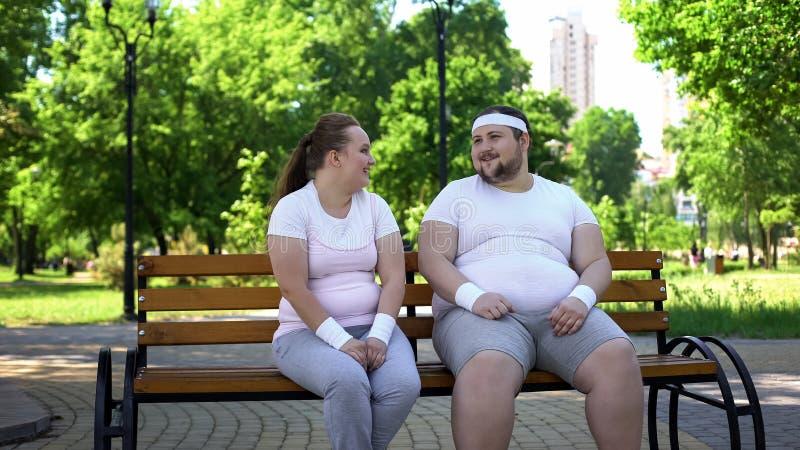 Vette mens die met zwaarlijvig mooi meisje, het vertellen grappen flirten, die onzekerheden overwinnen royalty-vrije stock foto