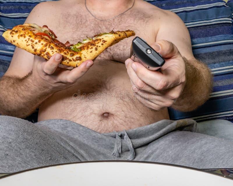 Vette mens die pizza eten en verre TV met behulp van royalty-vrije stock foto