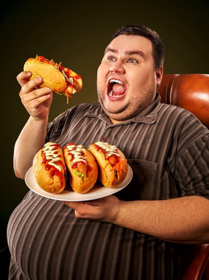 Vette mens die snel voedselhotdog eten Ontbijt voor te zware persoon stock foto