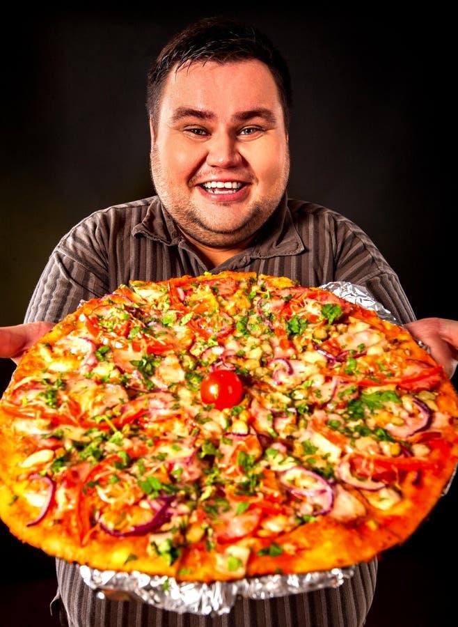 Vette mens die snel voedselpizza eten Ontbijt voor te zware persoon royalty-vrije stock afbeelding