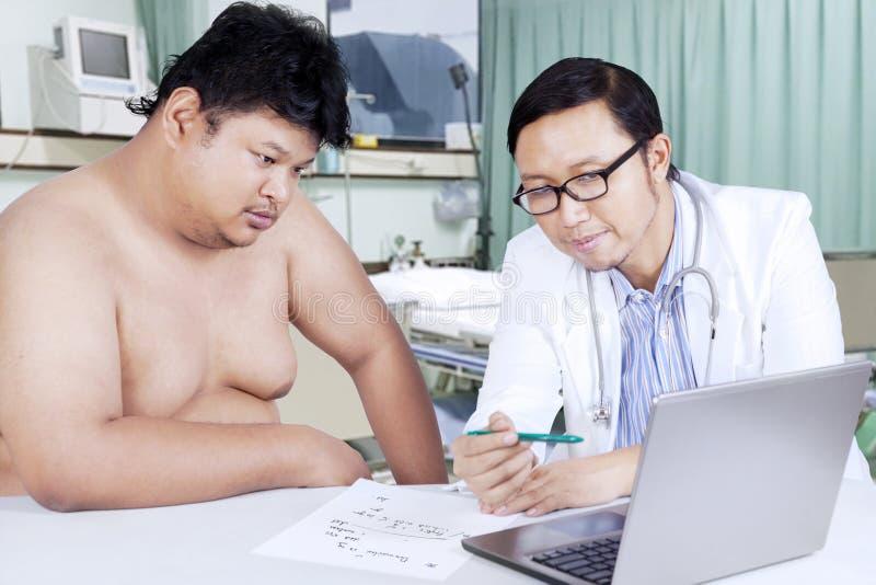 Vette mens en arts die medisch resultaat bekijken stock afbeelding