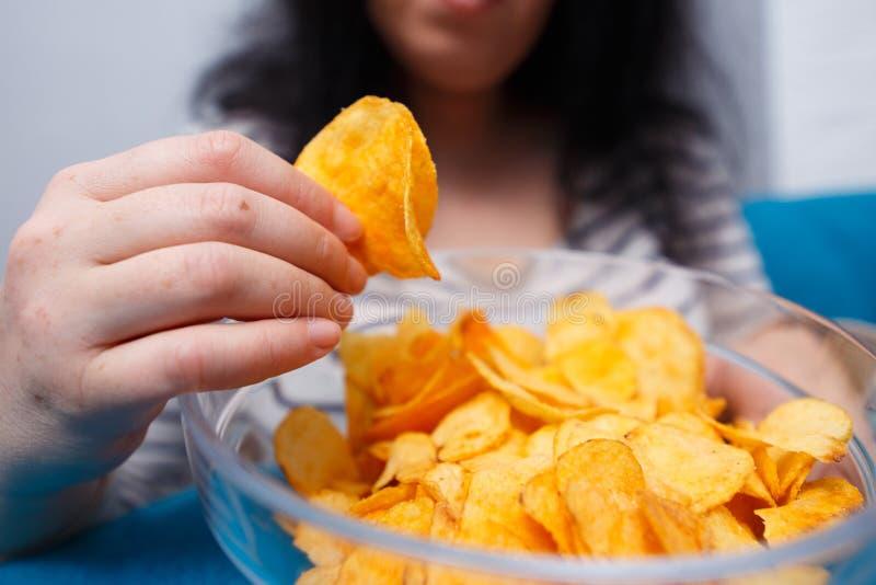 Vette vrouw die aan spaanders bereiken Het ongezonde eten, slechte gewoonten, voedsel stock foto