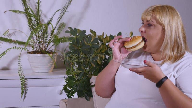 Vette vrouw die een hamburger eten, lettend op TV en laughes stock afbeeldingen