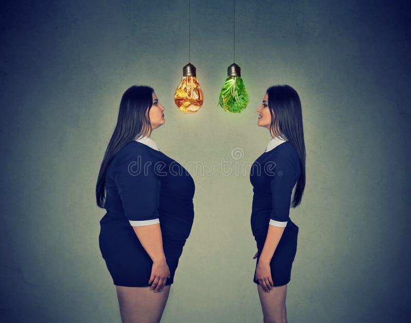 Vette vrouw die gelukkig slank geschikt meisje bekijken Het concept van de dieetkeus stock afbeeldingen