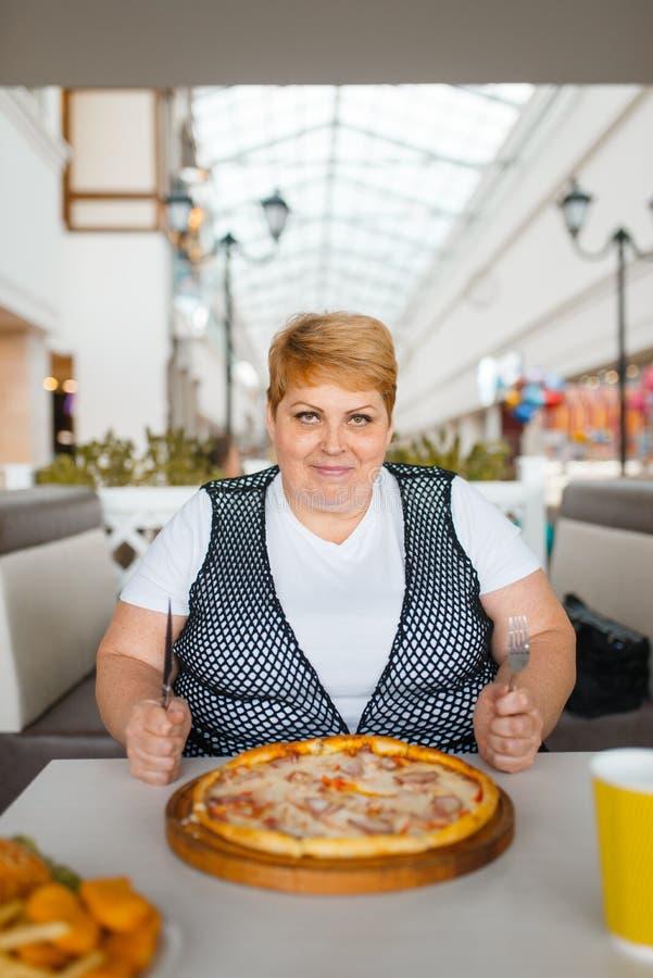 Vette vrouw die pizza in fastfood restaurant eten stock afbeeldingen