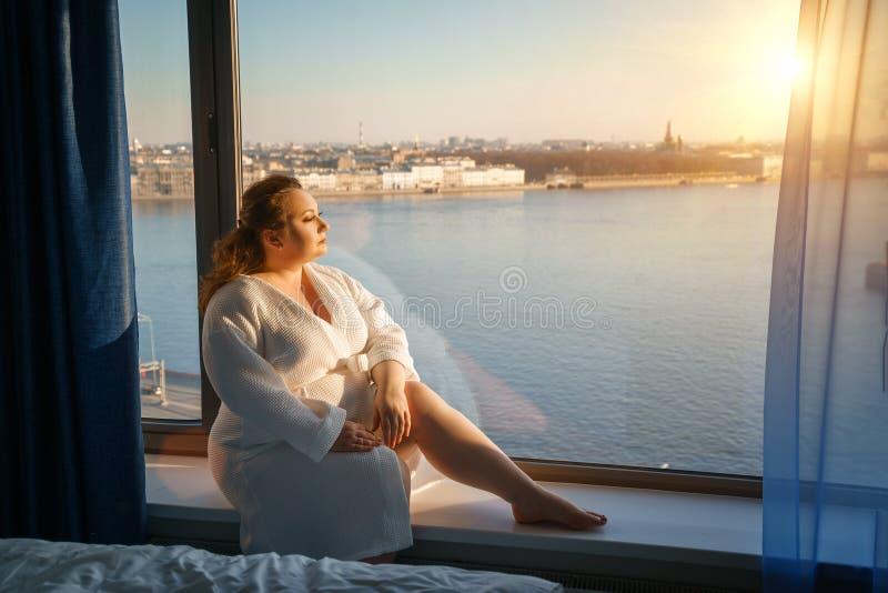 Vette vrouw die uit het venster, het concept bovenmatig gewicht kijken stock afbeelding