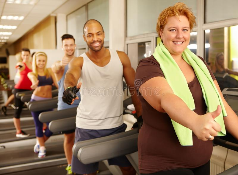 Vette vrouw die van opleiding in gymnastiek genieten stock foto