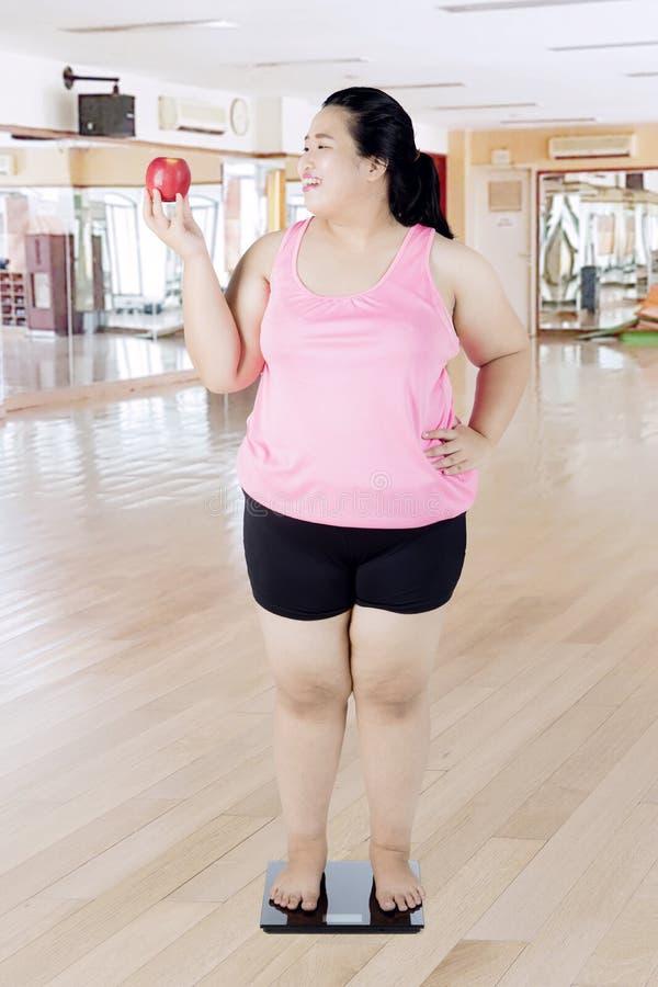 Vette vrouw die zich op de gewichtsschaal bevinden stock fotografie