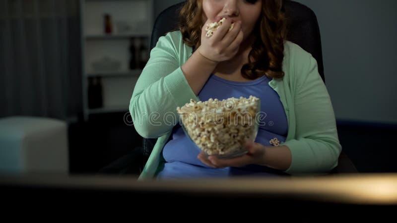 Vette vrouw die zoute popcorn eten en op TV, luiheid, passieve levensstijl letten stock foto