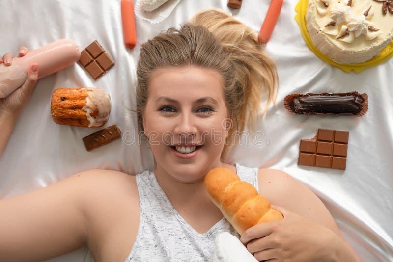 Vette vrouw met dessert die geschiktheidsschot doen stock foto