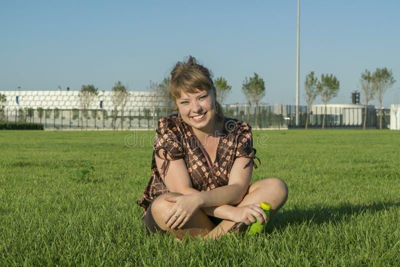 Vette vrouwenzitting op het groene gras royalty-vrije stock foto