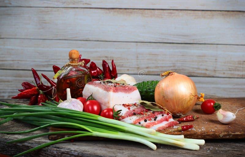 Vettig bacon met groenten en olijfolie op hakbord stock afbeeldingen