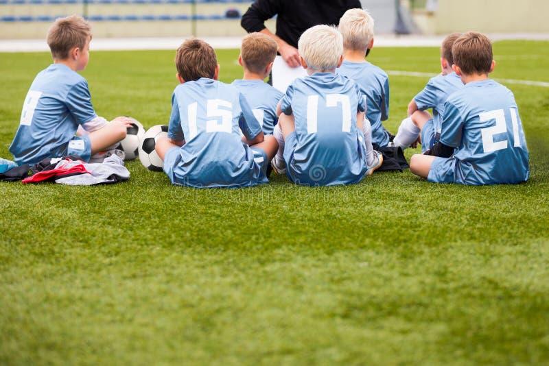 Vettura che dà le giovani istruzioni della squadra di calcio Calcio Team With Coach della gioventù fotografie stock libere da diritti