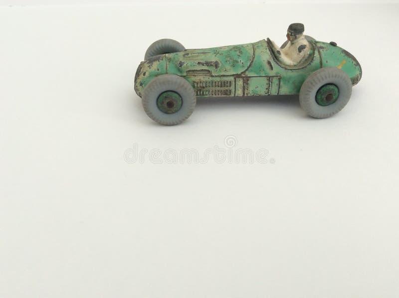 Vettura da corsa del giocattolo d'annata con l'autista, pittura verde indossata, diagonale su un fondo bianco con lo spazio della immagini stock libere da diritti