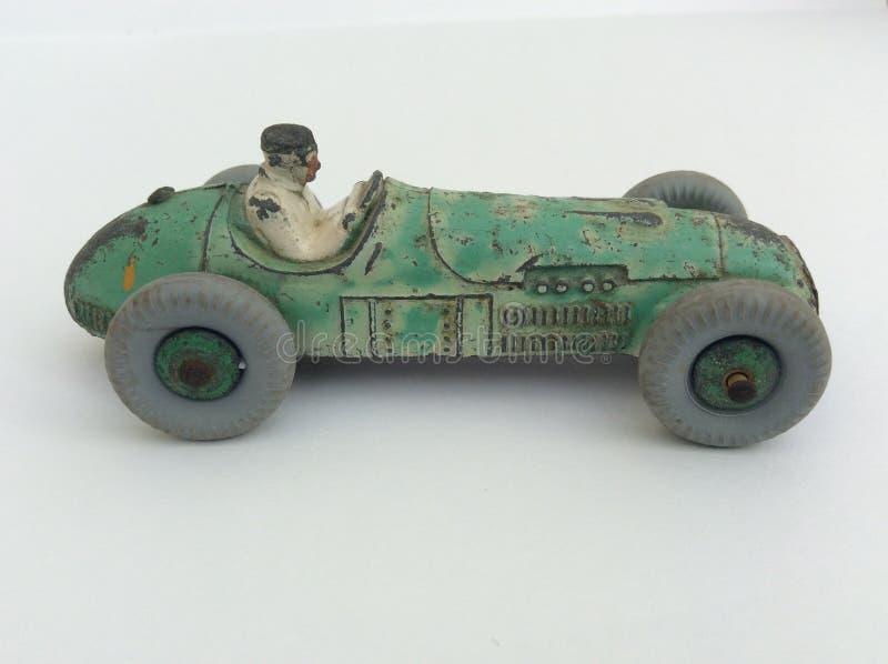 Vettura da corsa del giocattolo d'annata con l'autista, pittura verde indossata su un fondo bianco con lo spac della copia fotografie stock libere da diritti