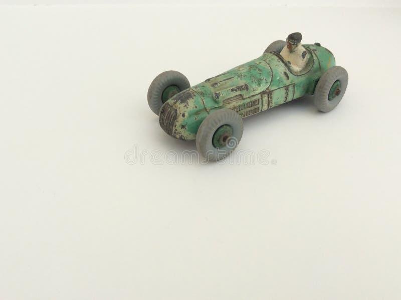 Vettura da corsa del giocattolo d'annata e autista, pittura verde indossata, su un fondo bianco con lo spazio della copia immagine stock