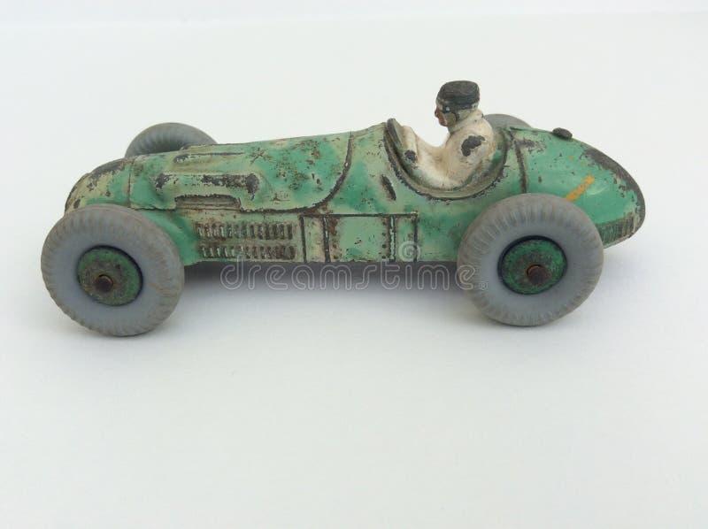 Vettura da corsa del giocattolo d'annata e autista, pittura verde indossata su un fondo bianco con lo spazio della copia immagini stock libere da diritti