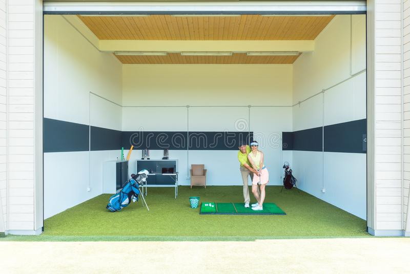 Vettura dedicata di golf facendo uso di attrezzatura moderna mentre insegnando ad una giovane donna fotografie stock