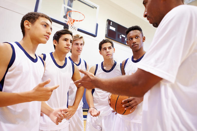 Vettura maschio di Team Having Team Talk With di pallacanestro della High School fotografie stock libere da diritti