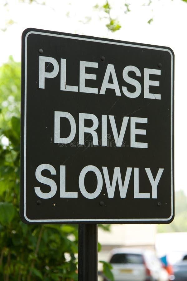 Veuillez piloter lentement le signe images stock